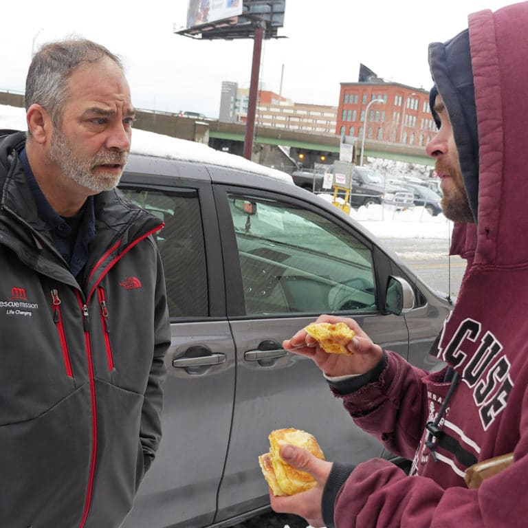 A Rescue Mission staff member providing outreach for a homeless community member