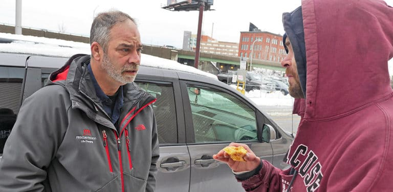 A Rescue Mission staff member providing outreach to a homeless man in Syracuse