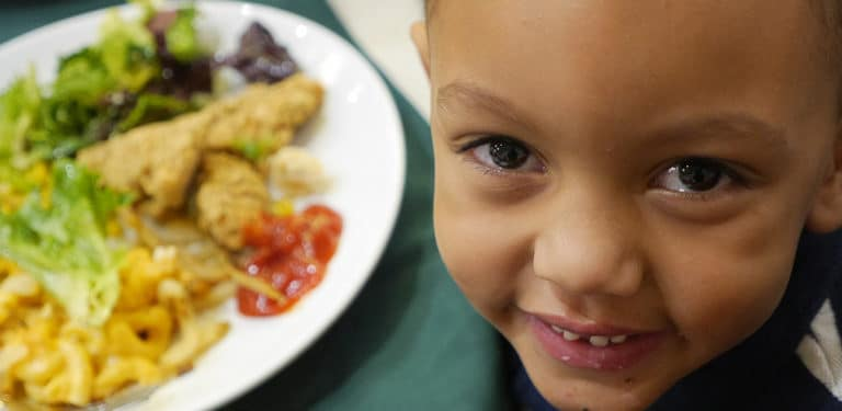 A child with a plate of food at The Rescue Mission